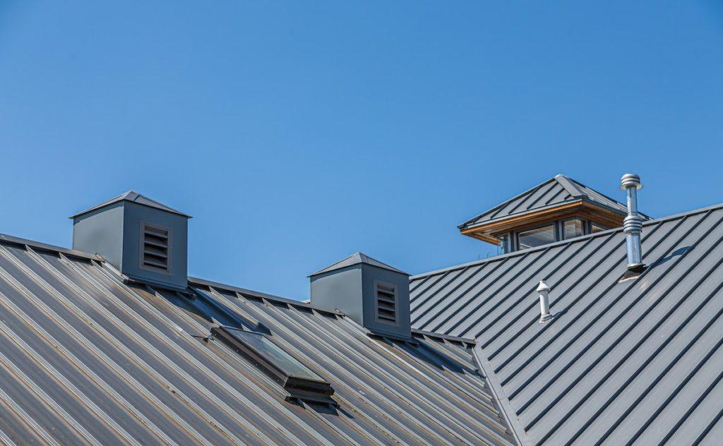 Ribbed Metal Roof and Cupolas Under Blue Skies